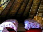 Four single beds upstairs on a mezzanine floor in Lothlorien Cottage in Hogsback, South Africa